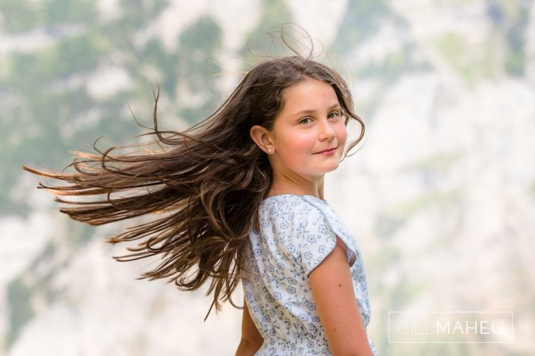 young girl spinning around hair flying at summer sun lifestyle photography session in Gimmelwald a mountain village near Bern, Switzerland by Lifestyle photographer Gill Maheu Photography, photographe de famille