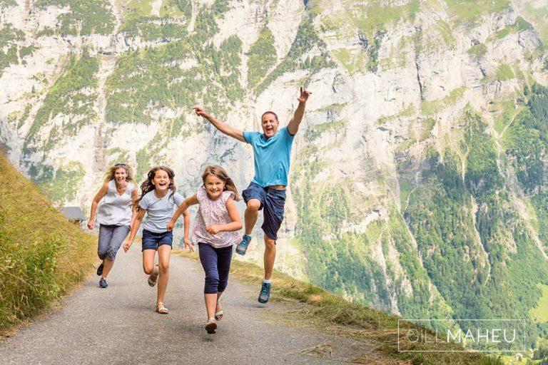 family run towards camera along mountain road in summer sun lifestyle photography session in Gimmelwald a mountain village near Bern, Switzerland by Lifestyle photographer Gill Maheu Photography, photographe de famille