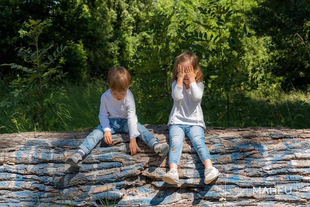 young brother and sister playing peekaboo on a log on family session near Geneva, Switzerland by Lifestyle photographer Gill Maheu Photography, photographe de famille