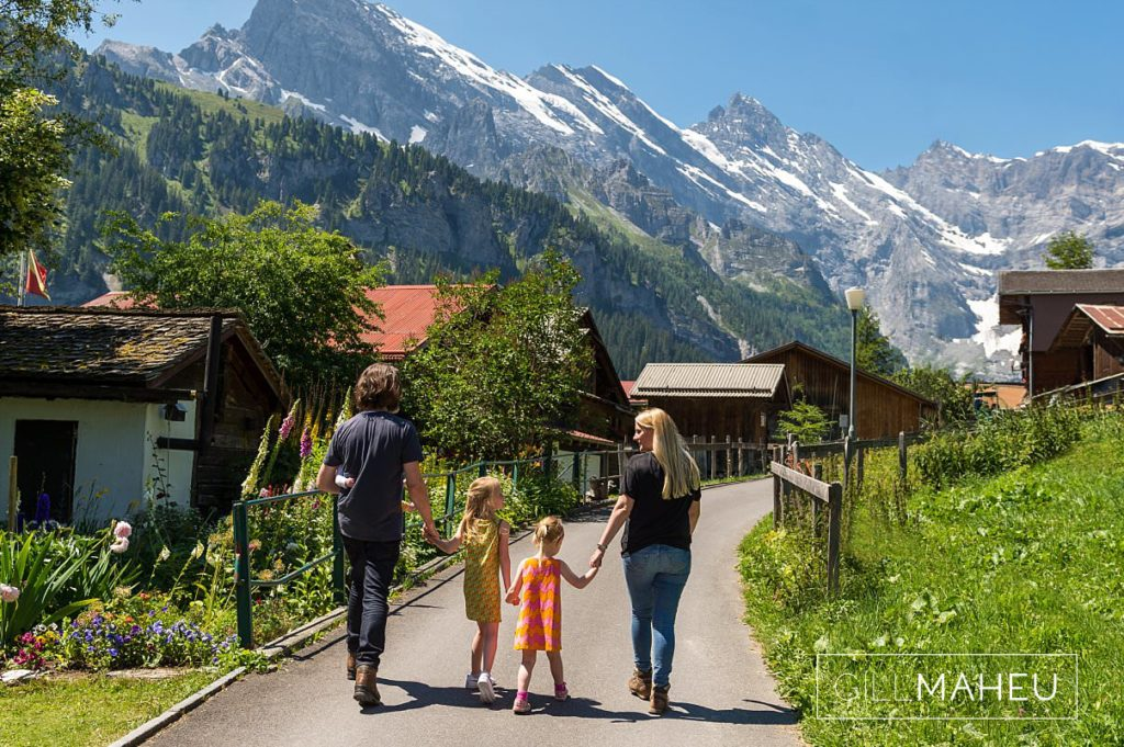 portrait of mum and dad and two daughters walking away from the camera at summer sun lifestyle photography session with beautiful young family in Gimmelwald, Switzerland by Lifestyle photographer Gill Maheu Photography, photographe de famille