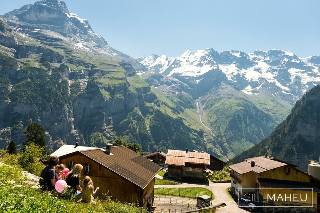 family of five admiring the spectacular view art  summer sun lifestyle photography session with beautiful young family in Gimmelwald, Switzerland by Lifestyle photographer Gill Maheu Photography, photographe de famille