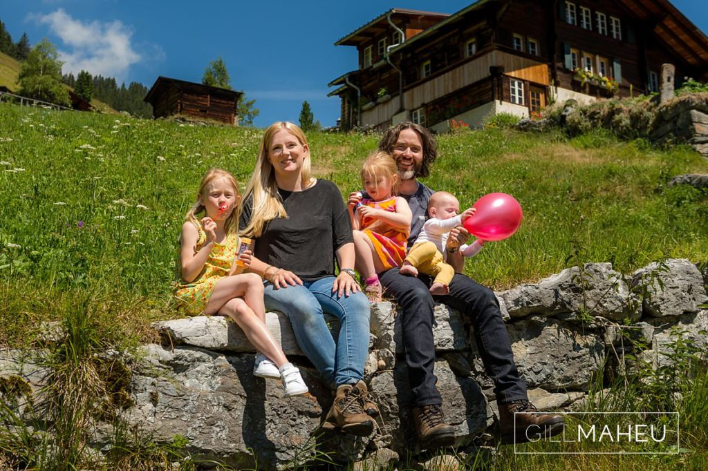 portrait of young family sitting on stone wall in the mountains at summer sun lifestyle photography session with beautiful young family in Gimmelwald, Switzerland by Lifestyle photographer Gill Maheu Photography, photographe de famille