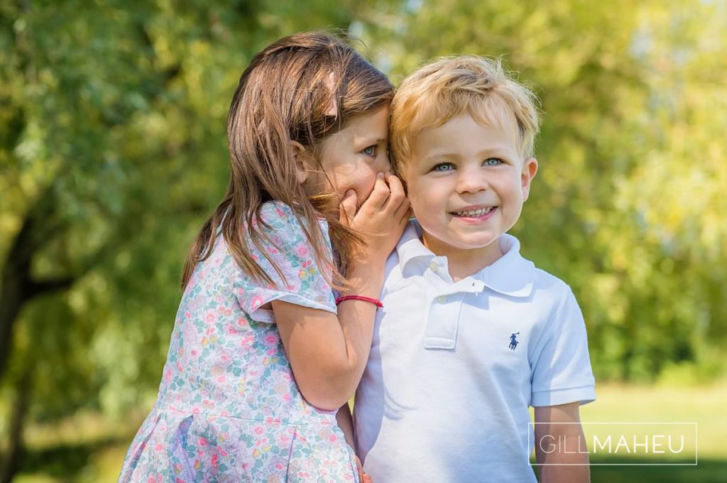 portrait of young girl whispering secrets in her little brother's ear at summer sun lifestyle photography session with beautiful young family in Lausanne by Lifestyle photographer Gill Maheu Photography, photographe de famille