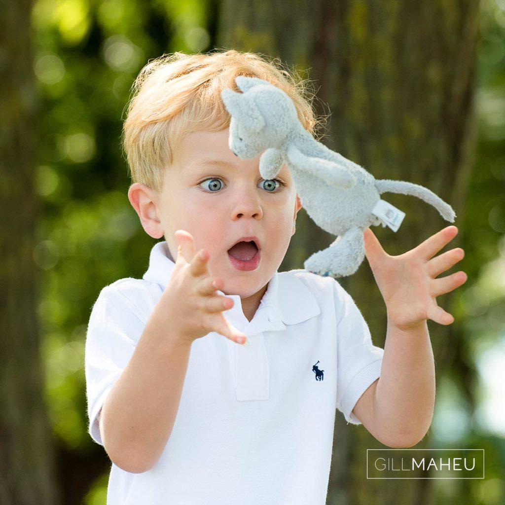 portrait of young boy throwing and catching his favourite toy at summer sun lifestyle photography session with beautiful young family in Lausanne by Lifestyle photographer Gill Maheu Photography, photographe de famille