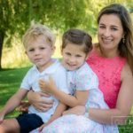 young mum having a cuddle with both children at summer sun lifestyle photography session with beautiful young family in Lausanne by Lifestyle photographer Gill Maheu Photography, photographe de famille