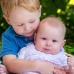 close up portrait of young boy and his baby sister at Lac Leman, Lausanne, Switzerland by Lifestyle photographer Gill Maheu Photography, photographe de famille