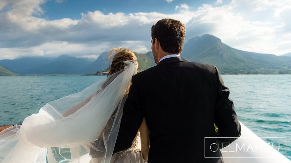 bride and groom looink into distance on speed boat on lake annecy at Abbaye de Talloires, Annecy wedding by Gill Maheu Photography, photographe de mariage