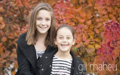family lifestyle portrait teenage sisters in front of glorious autumn coloured leaves by Gill Maheu Photography, photographe de famille et lifestyle