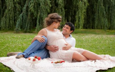 Future parents having a strawberry picnic in maternity session in Parc de la Tete D'or in Lyon, by Gill Maheu Photography, photographe de Grossesse et lifestyle