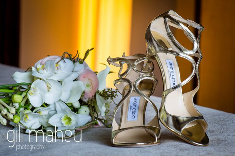close up details of stunning white arum lily and anenome wedding bouquet with strappy gold Jimmy Choo high heel shoes, Geneve wedding by Gill Maheu Photography, photographe de mariage