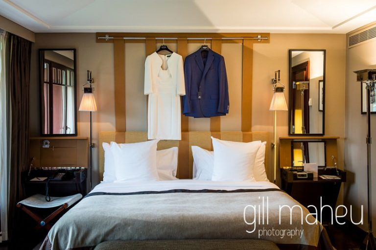 his and hers wedding outfits hanging above the bed at Hotel La Reserve, Geneve wedding by Gill Maheu Photography, photographe de mariage