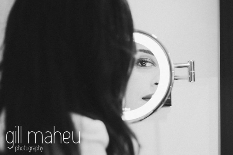 black and white shot of beautiful bride finishing her make up in mirror at Hotel La Reserve, Geneve wedding by Gill Maheu Photography, photographe de mariage