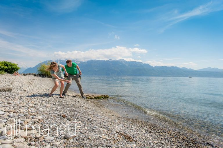 engaged couple skimming stones on shores of Lake Geneva on  speed boat on Lac Léman, Lausanne engagement session by Gill Maheu Photography, photographe de mariage