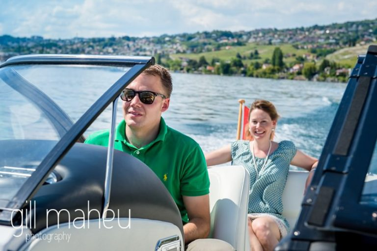 groom piloting boat with bride laughing in the background on speed boat on Lac Léman, Lausanne engagement session by Gill Maheu Photography, photographe de mariage