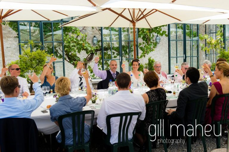raising a glass in celebration during wedding dinner at Chateau de Coppet, Geneva wedding by Gill Maheu Photography, photographe de mariage