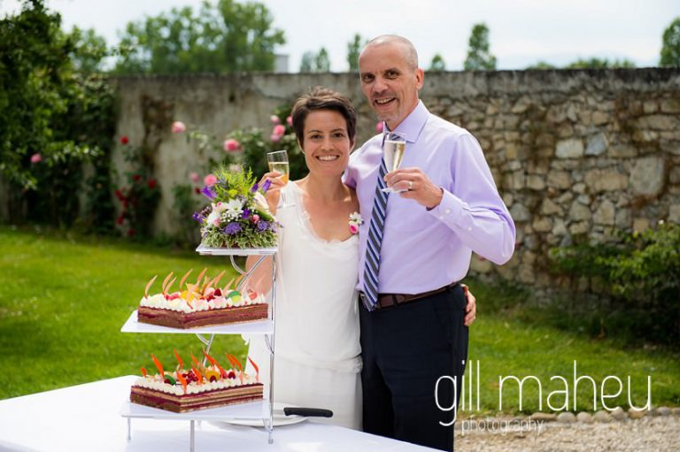 bride and groom with fruit covered piece montee wedding cake at Chateau de Coppet, Geneva wedding by Gill Maheu Photography, photographe de mariage
