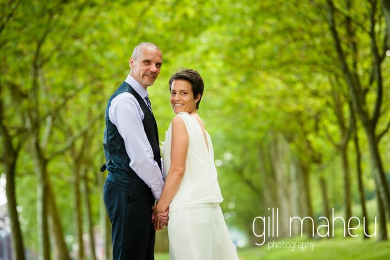 beautiful photo of bride and groom hand in hand in alley of trees looking at the camera Chateau de Coppet, Geneva wedding by Gill Maheu Photography, photographe de mariage