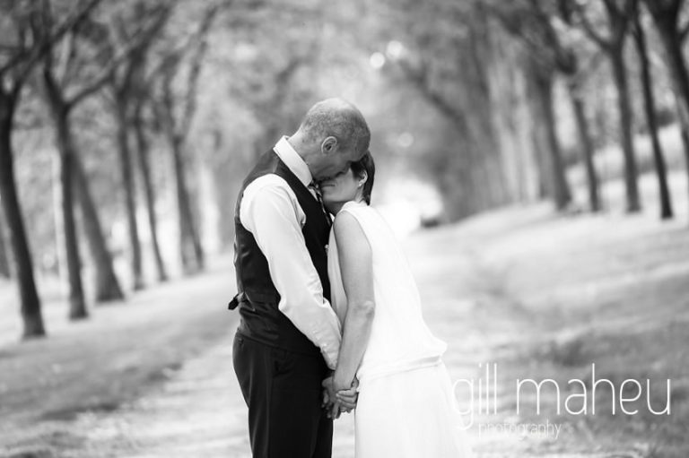 black and white photo of bride and groom kissing in alley of trees Chateau de Coppet, Geneva wedding by Gill Maheu Photography, photographe de mariage