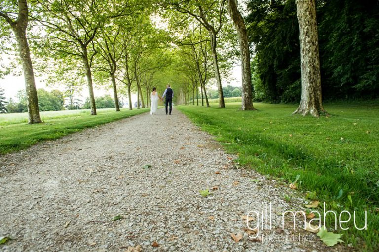 wedding couple in the distance at end of ally of trees in the grounds of Chateau de Coppet, Geneva wedding by Gill Maheu Photography, photographe de mariage