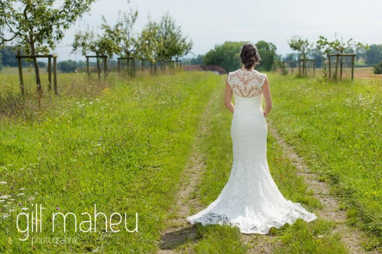 portrait of beautiful bride in Monique l'huillier lace wedding dress walking away from the camera on Geneva love the dress day after session by Gill Maheu Photography, photographe de mariage