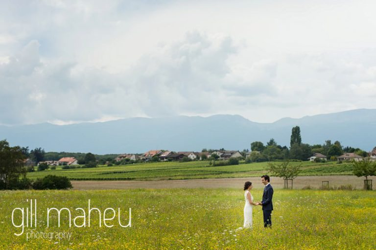 wide angle shot of bride and groom walking away from camera in a field of golden flowers on Geneva love the dress day after session by Gill Maheu Photography, photographe de mariage