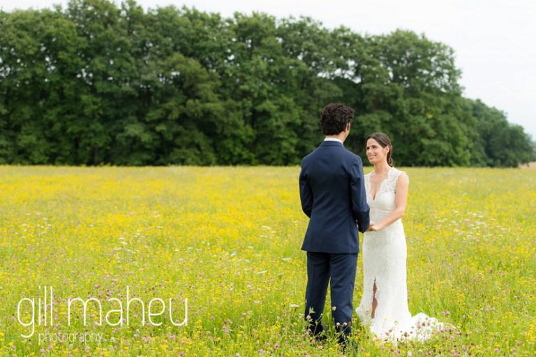 bride and groom hand in hand in a field of golden flowers on Geneva love the dress day after session by Gill Maheu Photography, photographe de mariage
