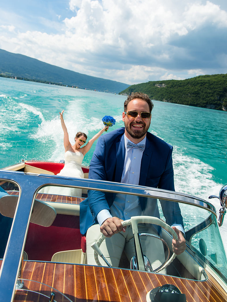 wedding portrait of bride and groom celebrating on mahogany Riva boat on Lake Annecy near Talloires by Gill Maheu Photography, photographe de mariage