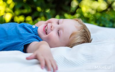 close up portrait of young boy lying on back laughing at Lac Leman, Lausanne, Switzerland by Lifestyle photographer Gill Maheu Photography, photographe de famille