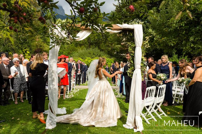 bride and groom under wedding arch during ceremony at Abbaye de Talloires, Annecy wedding by Gill Maheu Photography, photographe de mariage