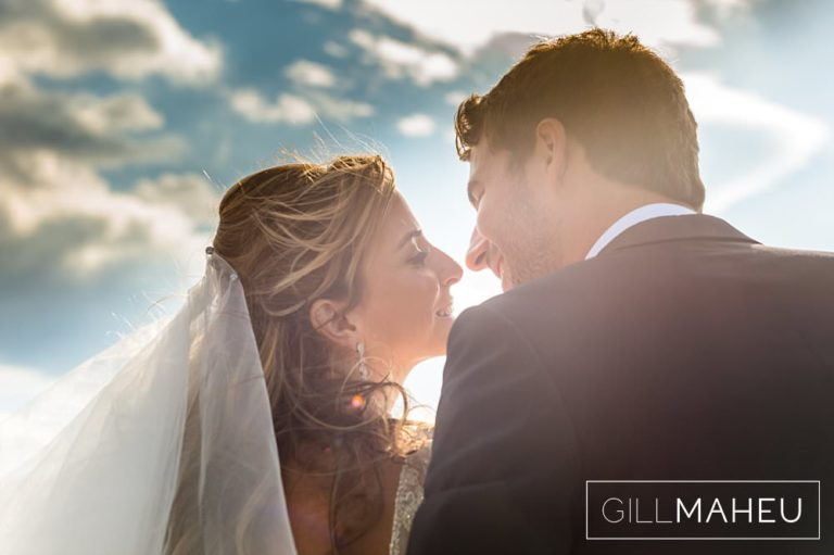 very romantic portrait of bride and groom kissing against the setting sun in Abbaye de Talloires, Annecy wedding by Gill Maheu Photography, photographe de mariage