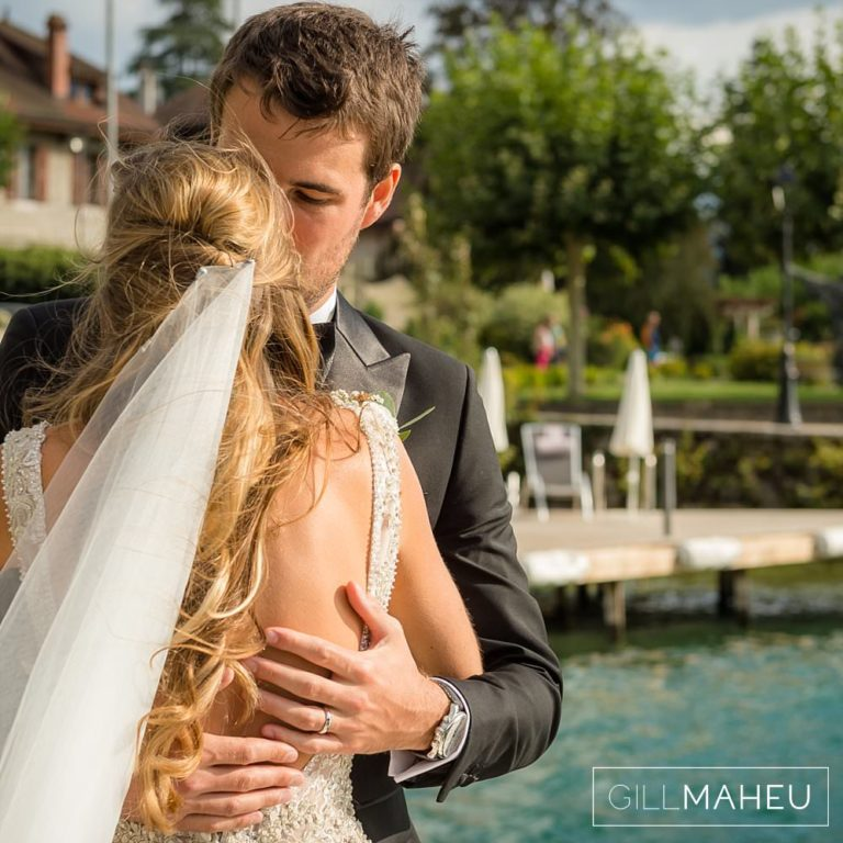 bride and groom embracing by the lake side in the evening sunshine at Abbaye de Talloires, Annecy wedding by Gill Maheu Photography, photographe de mariage
