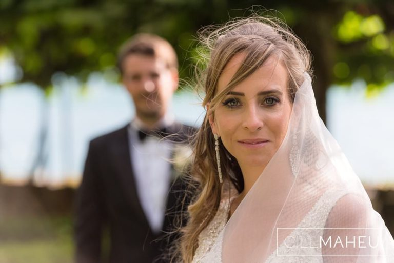 Beautiful Bride with groom in the background at tAbbaye de Talloires, Annecy wedding by Gill Maheu Photography, photographe de mariage