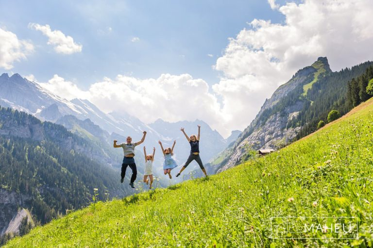 wide angle photo of mum and dad and two daughters jumping at summer sun lifestyle photography session in Gimmelwald a mountain village near Bern, Switzerland by Lifestyle photographer Gill Maheu Photography, photographe de famille