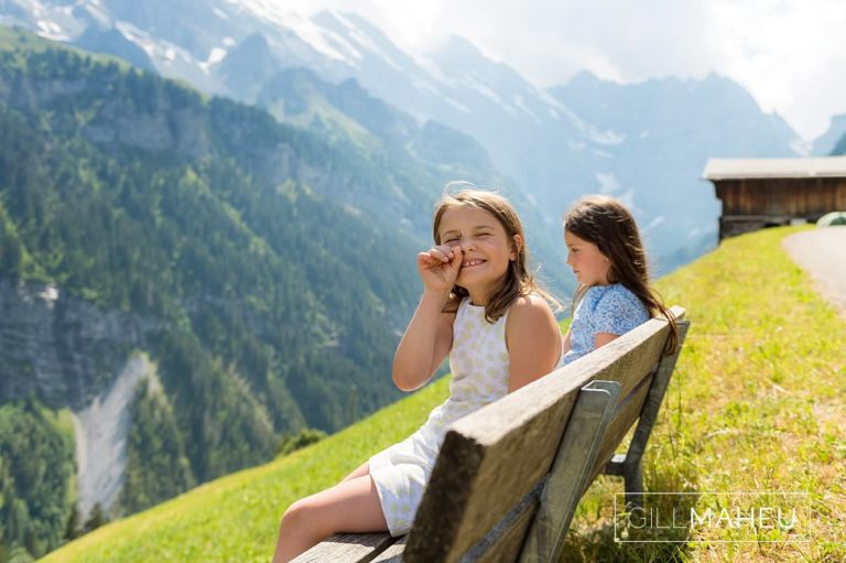 two young sisters sitting on bench admiring spectacular view in summer sun lifestyle photography session in Gimmelwald a mountain village near Bern, Switzerland by Lifestyle photographer Gill Maheu Photography, photographe de famille