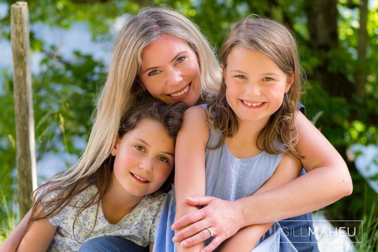 close up of mum and two daughters cuddling at summer sun lifestyle photography session with beautiful young family in Gimmelwald, Switzerland by Lifestyle photographer Gill Maheu Photography, photographe de famille