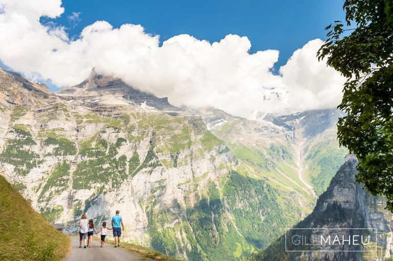 young family hugging in front of spectacular view in summer sun lifestyle photography session in Gimmelwald a mountain village near Bern, Switzerland by Lifestyle photographer Gill Maheu Photography, photographe de famille