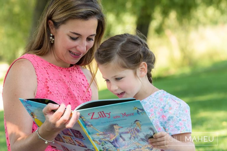 Little girl practising her reading with her mummy during summer sun lifestyle photography session with beautiful young family in Lausanne by Lifestyle photographer Gill Maheu Photography, photographe de famille